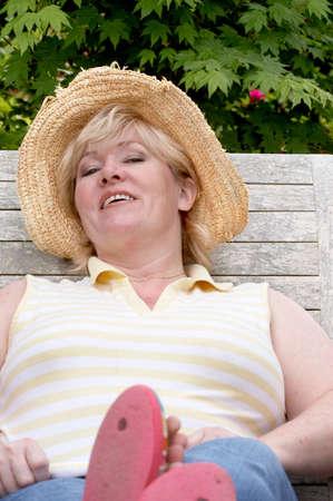 flip flops: Mature woman resting in garden chair