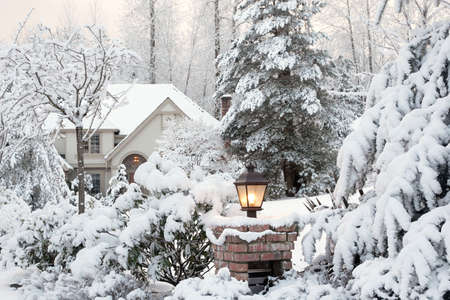 home garden: Driveway light and house on a snowy morning Stock Photo