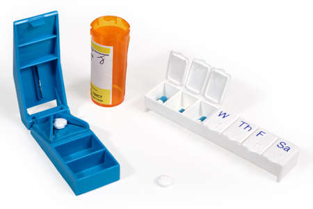weekly: Pill cutter and weekly storage box with medicine bottle and pills