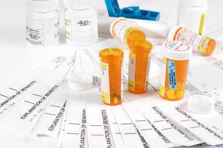 Medicine bottles, storage containers and medical insurance statements photo