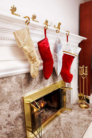Four Christmas stockings hanging at the fireplace photo