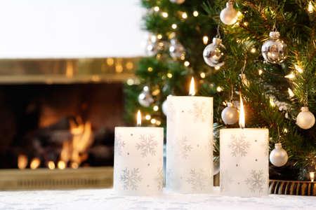 camino natale: Candele fiocco di neve e decorazioni scintillanti di un caldo fuoco