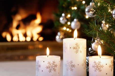 camino natale: Candele fiocco di neve e decorazioni scintillanti illuminato dal fuoco tremolante Archivio Fotografico