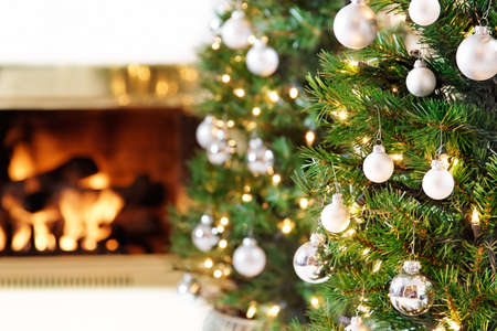 christmas fireplace: Glittering silver and white Christmas tree decorations by a warm fire Stock Photo