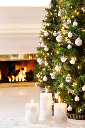 fireplace living room: Snowflake candles and glittering decorations by a warm fire Stock Photo