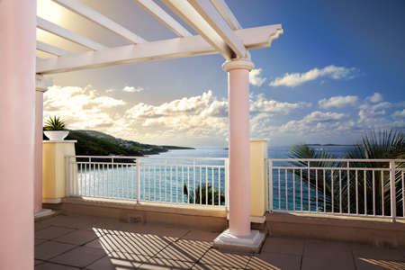 balcony: Cliff-top terrace looking out over tropical hills & ocean Stock Photo