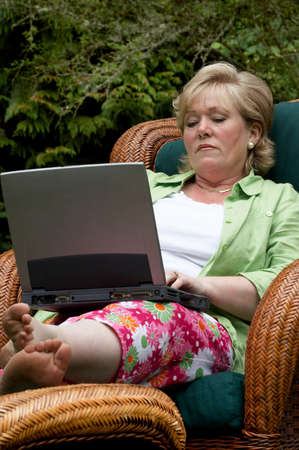 laptop: Mature woman working at a laptop outside