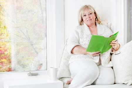 reading material: Mature woman relaxing with some good reading material