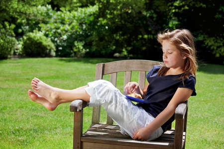 little girl barefoot: Young girl relaxes in the garden eating her afternoon snack