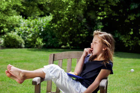 Young girl relaxes in the garden eating her afternoon snack photo