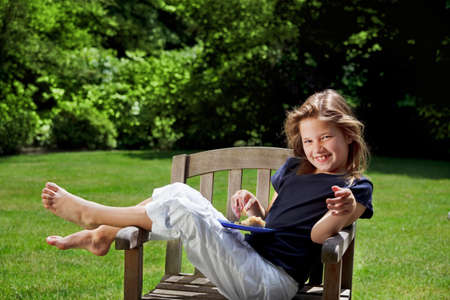Young girl giggling in the garden with an afternoon snack Stock Photo - 9925850