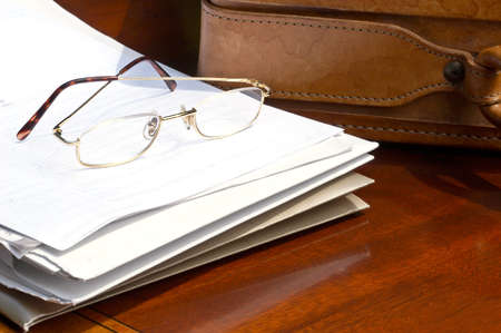 eyestrain: Papers and reading glasses beside leather briefcase