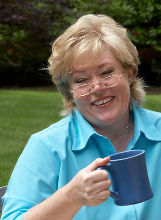 Mature woman laughing over a mug of coffee photo