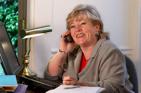 Mature businesswoman laughs during phone conversation photo