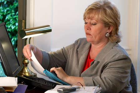 Mature businesswoman putting paper into an inter-office envelope photo