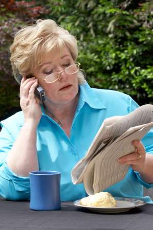 financials: Mature woman reading financials and making a call
