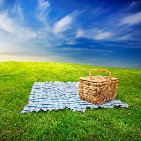 picnic blanket: Manta de picnic y cesta en la hierba con cielo dram�tico twilight