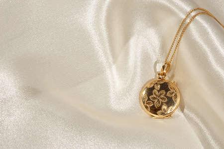 medaglione: Engraved gold locket on cream satin