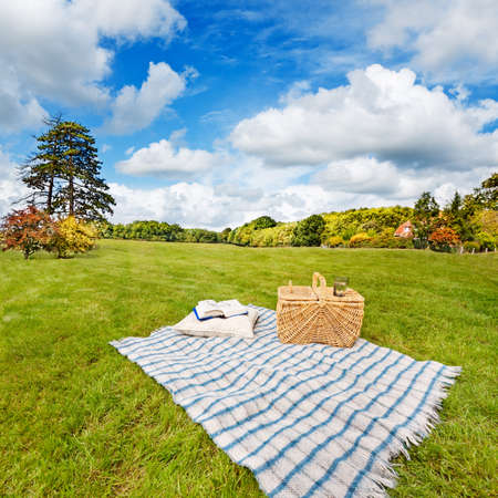 Picnic blanket, cushion, basket & pillow in a rolling field photo