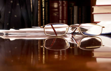near sighted: Reading glasses on desk piled with work. Focus is on glasses