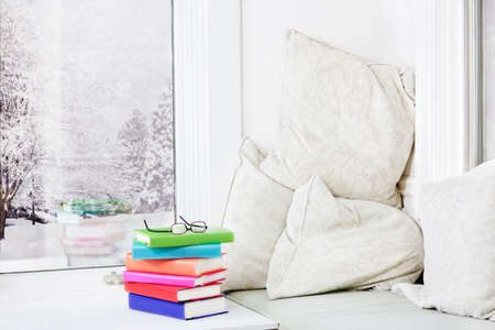 Window seat with comfy cushions and a stack of books photo