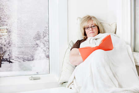 Mature woman lying down reading under a warm blanket photo