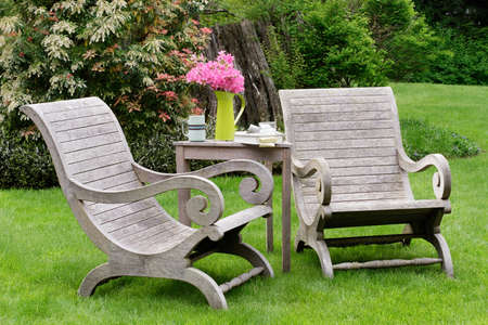 Wooden garden chairs in a green spot in the garden photo