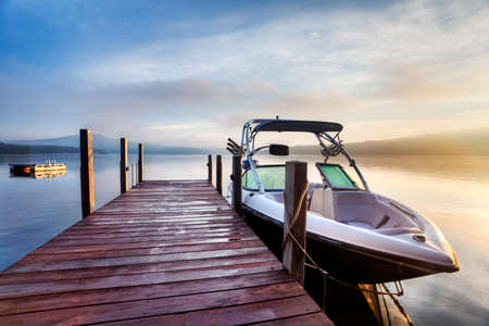 Sun and mist on a Summer New Hampshire boat dock at sunrise