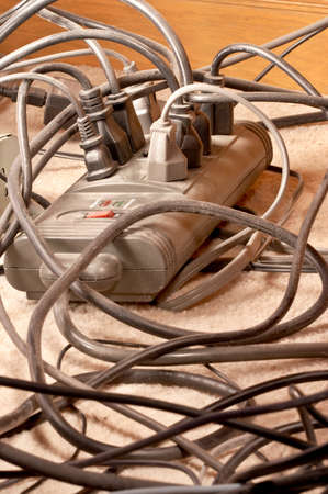 Power, network and phone cables, tangled and dusty under a desk photo
