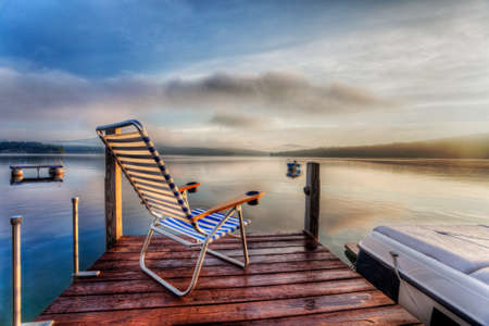 Chair sitting at the end of a dock in very early morning summer light photo