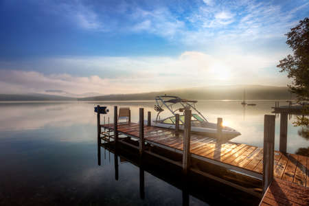 Sunrise through the clouds and mist over a calm New Hampshire lake Stock Photo - 11295331