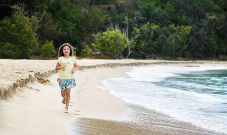 little girl barefoot: Young girl running along the beach at water