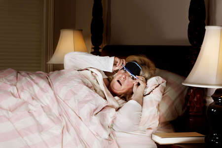 Mature woman looks disturbed by what she sees lifting the eye mask photo