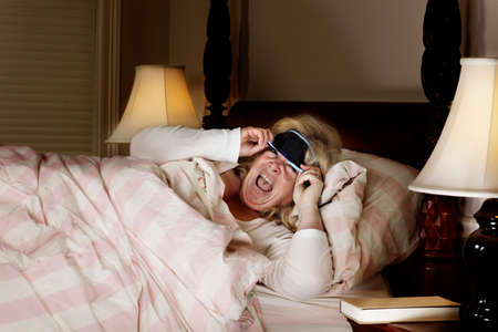 Mature woman lscreams at  what she sees lifting the eye mask photo