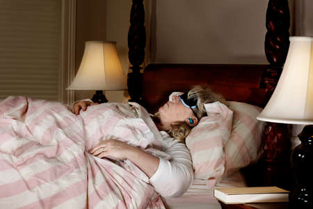 sleep mask: Mature woman in bed with sleep mask and ear plugs