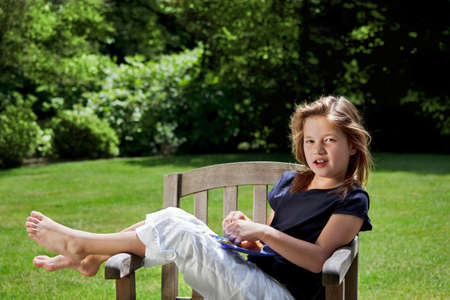 Young girl relaxes in the garden with an afternoon snack photo