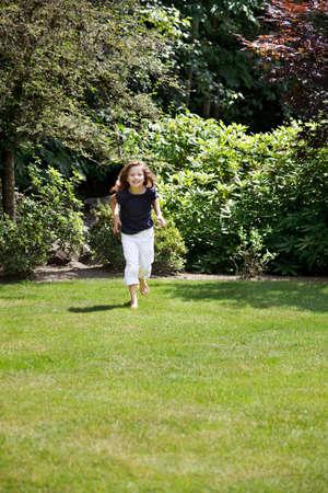 Young girl runs across the grass photo