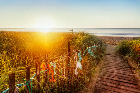 Sun at the horizon lights dunes and old-fashioned boardwalk on a Maine beach photo