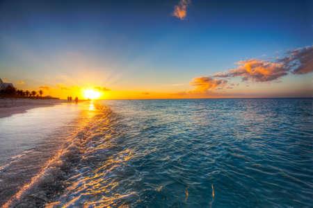 turks: Grace Bay Beach, Islas Turcas y Caicos, con la puesta del sol en el horizonte