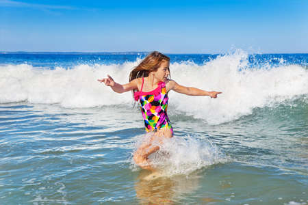 Young girl turning to run from an incoming wave photo