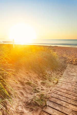 Early morning sun floods the sand dunes and sign on a Manie beach photo