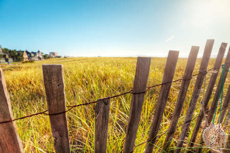 early summer: Broken down boardwalk fence in Maine sand dunes early on a summer morning Stock Photo