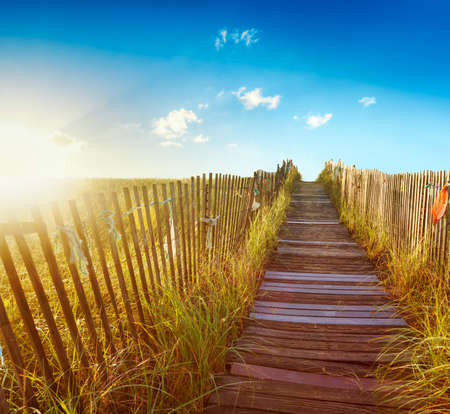 Wooden boardwalk through the dunes to a Maine beach at sunrise photo