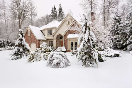 Suburban house with snow on the ground and more falling photo