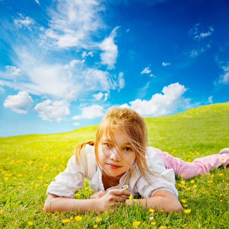 Young girl lies in the buttercup strewn grass in a sunny meadow photo