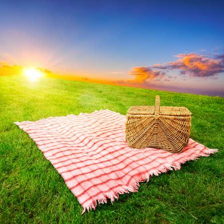 picnic blanket: Manta de picnic y una cesta en un prado cubierto de hierba iluminada por el sol Foto de archivo