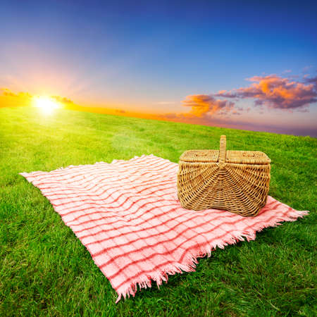 basket: Picnic blanket and basket in a sunlit grassy meadow