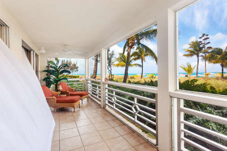 Billowing white curtains on a sunny screen in porch with an oceanfront view photo