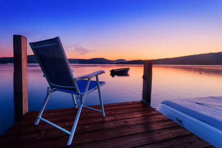 Chair at the end of the dock on a calm summer morning photo
