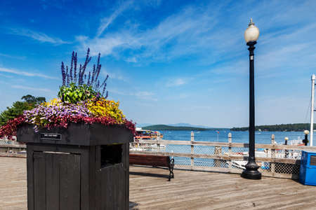 The boardwalk in Weirs Beach, New Hampshire on a summer afternoon, looking out over Lake Winnipesaukee photo